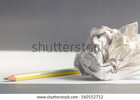 Pencil on clear white paper with crumble paper ball - stock photo