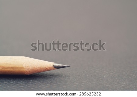 Pencil on empty grey background - stock photo