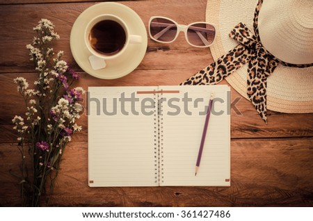 Pencil on notebook Include sunglasses, tea cup, hat and flower on the wooden background.