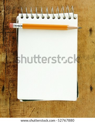 Pencil on small pad of paper blank for your text. - stock photo