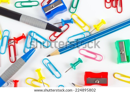 Pencil, pen, paperclips, sharpeners and thumbtacks on white desktop close up - stock photo