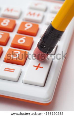 pencil pushing addition button on calculator - stock photo