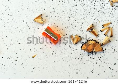 Pencil sharpener and shavings on white background. - stock photo