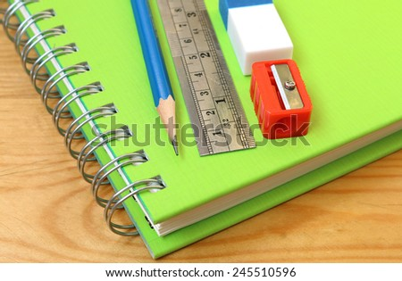 Pencil sharpener, eraser stick and put top a notebook. - stock photo