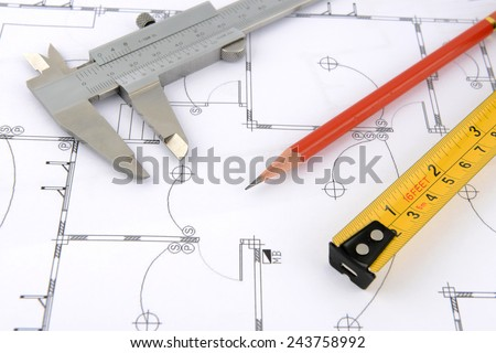 pencil, vernier caliper and measuring tape on plans - stock photo