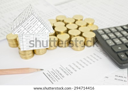 Pencil with house on pile of gold coins and calculator on finance account.
