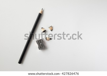 Pencil with sharpening shavings on white background - stock photo