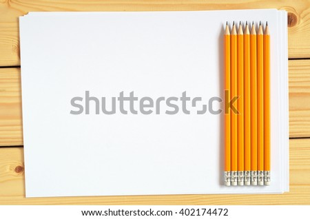 Pencils and a blank sheet of paper on wooden desk, top view - stock photo