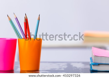 Pencils and book on table