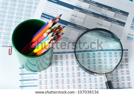 pencils and magnifying glass over reports