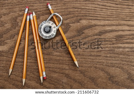 Pencils and school lock on wood surface - stock photo