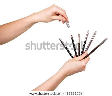 Pencils for make-up in female hands isolated on white background.