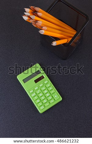 Pencils in the stand and the calculator on a black background. The view from the top