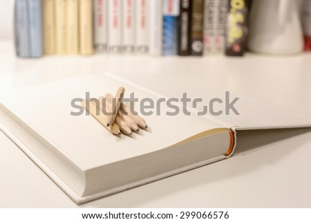 Pencils on a blank note book with a stack of textbooks in the background. The image with selective focus and shallow depth of field. - stock photo