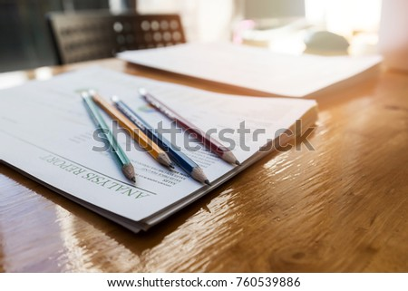 Pencils on report paper on wooden desk at the office