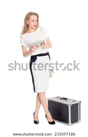 Pending the pretty girl with a tablet PC and with a suitcase - stock photo