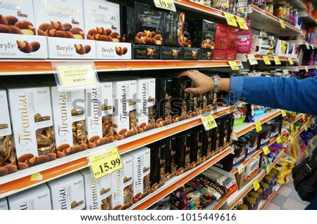 Pengkalan Kubur, Malaysia - January 27, 2018 : A hand hold a chocolate in a hypermart with many type of chocolates in Kelantan