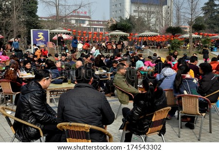 Pengzhou, China February 1, 2014:  Crowds of people sitting outside in Pengzhou City Park decorated with Chinese New Year lanterns drinking tea and playing cards
