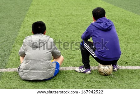 Pengzhou, Sichuan province, China  March 2, 2013:  Two Chinese youths, one sitting on a soccer ball, watching a game sitting on the astroturf at an outdoor stadium in Pengzhou, China. - stock photo