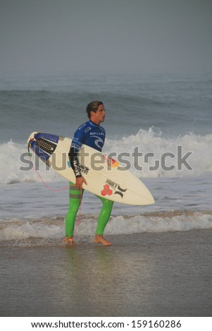 PENICHE, PORTUGAL - 2013 OCT 17: Julian Wilson exiting the water in round 4, heat 1 at WCT contest, Moche Rip Curl Pro Peniche, Portugal 17 October 2013  - stock photo