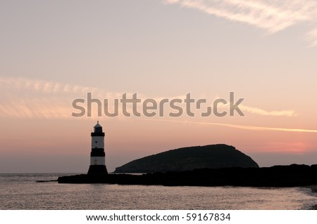 penmon Lighthouse with copy space at sunrise.