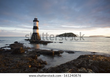 penmon point lighthouse at sunrise looking out to sea - stock photo