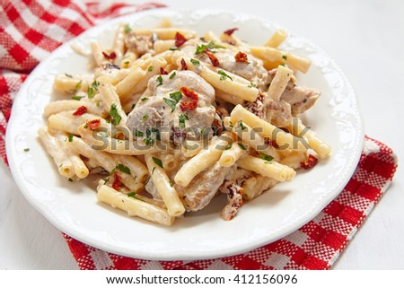 Penne pasta and chicken breasts with herbs and creamy sauce - stock photo