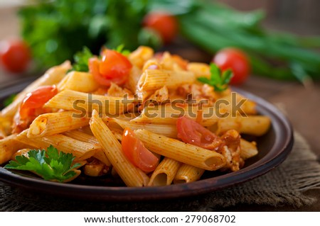 Penne pasta in tomato sauce with chicken, tomatoes decorated with parsley on a wooden table - stock photo