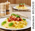 Penne pasta with a bolognese tomato beef sauce on the kitchen table - stock photo