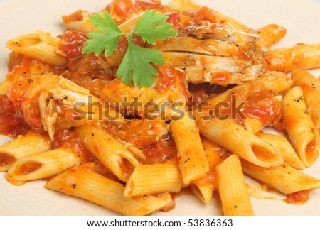 Penne pasta with chicken in arrabiata sauce - stock photo