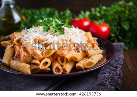 Penne pasta with chicken, tomato sauce, parmesan cheese and parsley on dark wooden background close up. Italian cuisine. - stock photo