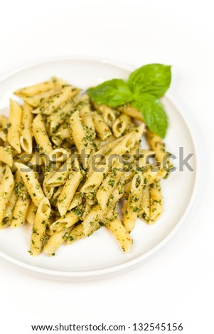Penne pasta with pesto sauce and fresh basil