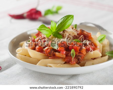 Penne pasta with sauce, cheese and basil, selective focus - stock photo