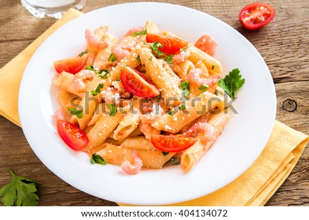 Penne pasta with shrimps, tomato sauce, parsley and grated parmesan cheese over rustic wooden background - stock photo