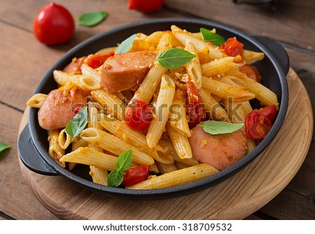 Penne pasta with tomato sauce with sausage, tomatoes, green basil decorated in a frying pan on a wooden background - stock photo