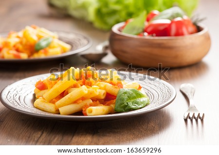 Penne pasta with tomatoes on a plate