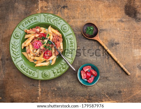 Penne pasta with tuna sauce and tomatoes in green plate on old wooden table,top view - stock photo