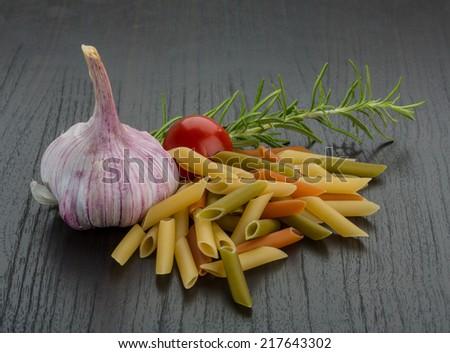 Penne - raw italian pasta with herbs - stock photo