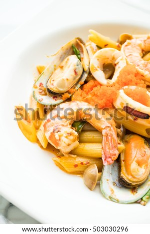 Penne seafood tom yum pasta in white plate - Italian food style