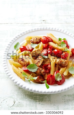 Penne with chicken and cherry tomatoes - stock photo