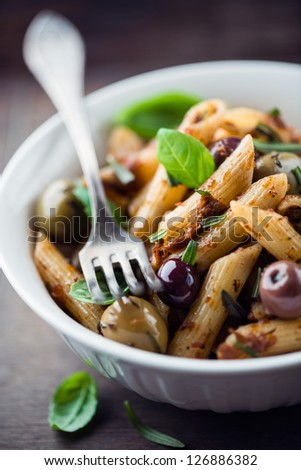 Penne with dried tomato pesto, olives and herbs - stock photo