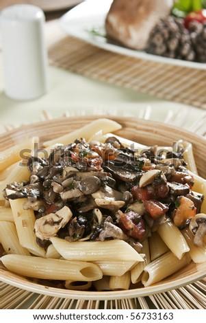 Penne with mushroom sauce. Food photography. Italian cuisine accompanied by mushroom sauce. - stock photo