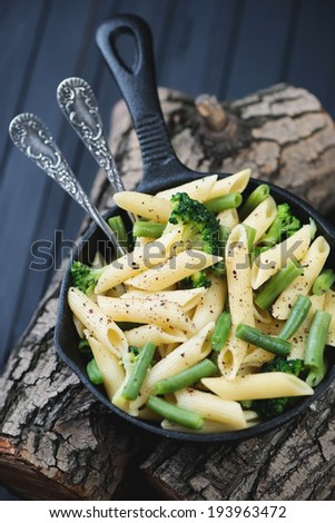 Penne with vegetables in a frying pan on wooden logs, close-up - stock photo