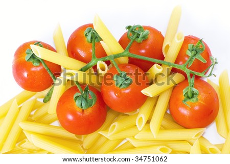 Pennette rigate and red cherry tomato on white dish with selective focus - stock photo