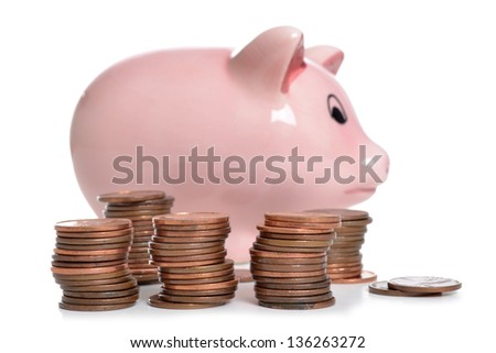 pennies and a piggybank white background - stock photo