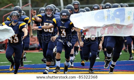 PENNSBURG, PA - SEPTEMBER 24: The Pope John Paul II high school football team break through a sign to take the field for the PAC10 conference game against Methacton September 24, 2011 in Pennsburg, PA