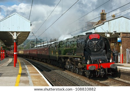 PENRITH, ENGLAND - JULY 28: Preserved steam locomotive 46233, Duchess of Sutherland, heads the Cumbrian Mountain Express through Penrith station on July 28, 2012, on the English West Coast mainline. - stock photo