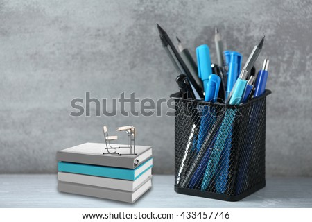 Pens and pencils in metal holder, notebooks with small wooden desk and chair on wall background - stock photo