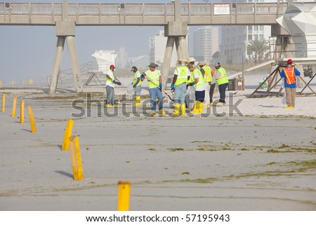 PENSACOLA BEACH - JULY 7: oil workers continue to clean the beach of oil on July 7, 2010 in Pensacola Beach, FL. - stock photo