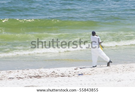 PENSACOLA BEACH - JUNE 23: A BP oil worker stands near the shore on June 23, 2010 in Pensacola Beach, FL. - stock photo